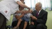 נשיא המדינה שמעון פרס מביט בילד המקבל את החיסון המוחלש נגד פוליו, 21.8.13 (צילום: פלאש 90)