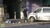 """עיתונאים נסים מהבניין בו שכנו אולפי תחנת """"אל-אקצא"""" של חמאס לאחר שהופצץ בידי צה""""ל, 18.11.13 (צילום מסך: RT)"""