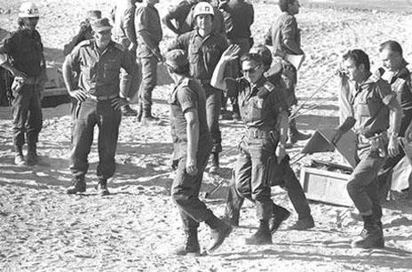 """אהרון יריב (במרכז, מנופף למצלמה), ראש צוות המשא-ומתן עם המצרים, מגיע לחתימת הסכם הפסקת האש ב""""קילומטר ה-101"""", 11.11.73 (צילום: לע""""מ)"""