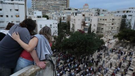 ישראלים צופים בהלוויית אריק איינשטיין מגג בניין סמוך, 27.11.13 (צילום: יעקב נחומי)
