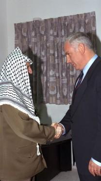 """בנימין נתניהו לוחץ את ידו של יאסר ערפאת. מחסום ארז, 4.9.1996 (צילום: משה מילנר, לע""""מ)"""
