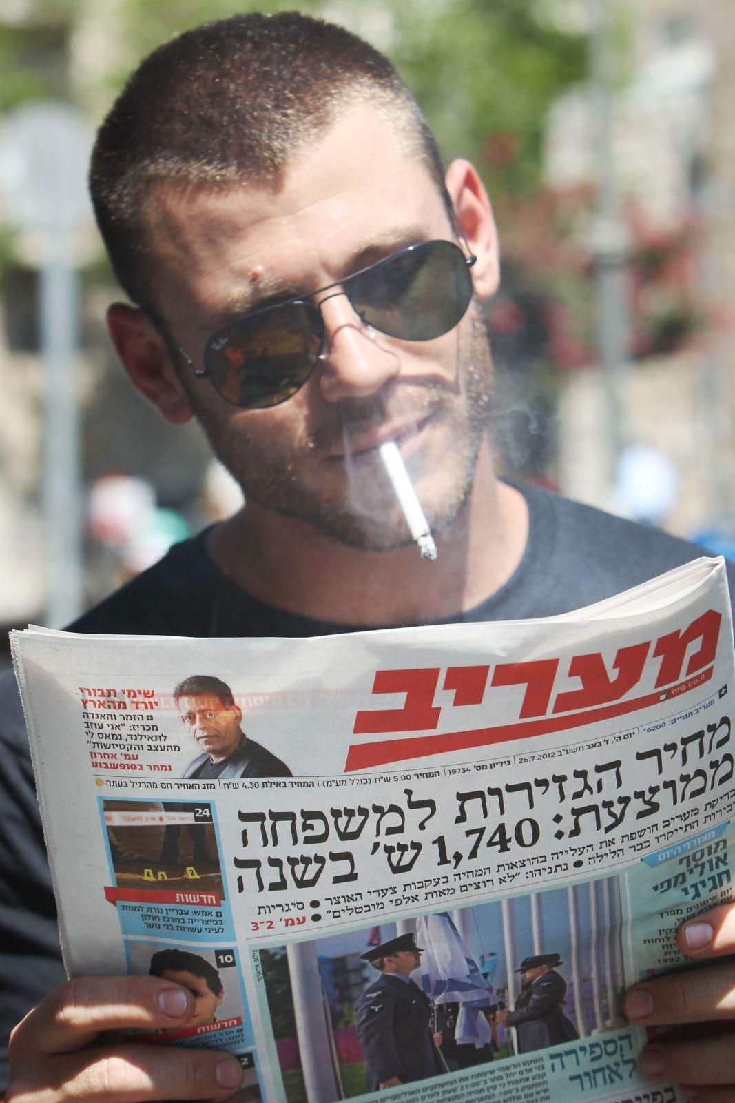 """ישראלי מעיין בגליון """"מעריב"""" מה-26 ביולי 2012, שכותרתו הראשית מדווחת בין היתר על העלאת המס על סיגריות (צילום: מרים אלסטר)"""