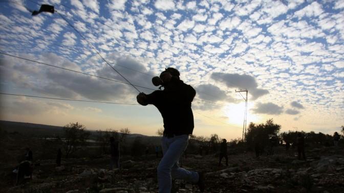 פלסטיני מיידה אבן לאחר לווייתו של סעיד ג'אסר עלי, בן 85, שלטענת עדי ראייה מת כתוצאה משאיפת גז מדמיע. 2.1.14 (צילום: עיסאם רימאווי)