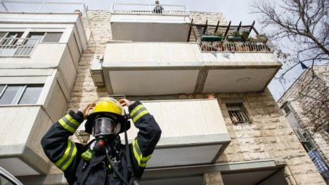 כבאי על רקע הדירה בירושלים שבה הורעלה משפחה מחומרי הדברה, 22.1.14 (צילום: פלאש 90)