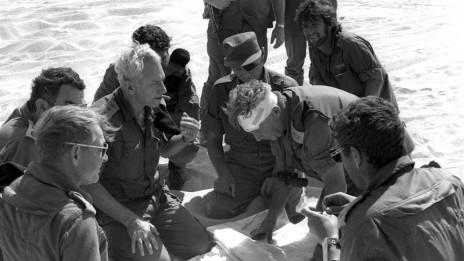 """האלוף אריאל שרון (עם תחבושת לראשו), משמאלו שר הביטחון משה דיין והרמטכ""""ל לשעבר חיים בר-לב, החזית המצרית במלחמת יום-כיפור, 17.10.1973(צילום: יוסי גרינברג, לע""""מ)"""