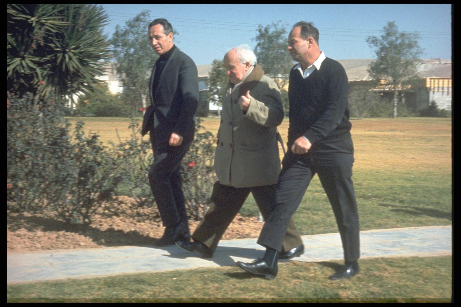 """דוד בן-גוריון בטיולו הרגלי היומי בקיבוץ שדה-בוקר בנגב. משמאל: שמעון פרס. 1.3.1969 (צילום: לע""""מ)"""