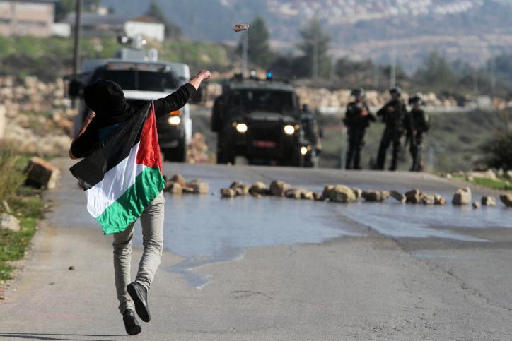 """פלסטיני מיידה אבנים לעבר חיילי צה""""ל בעת הפגנה נגד הרחבת היישוב חלמיש שליד נבי סאלח, 28.12.12 (צילום: עיסאם רימאווי)"""