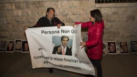 """מפגינים נגד שחרור מחבלים מסירים כרזה לאחר שנודע על ביטול """"הפעימה הרביעית"""" של שחרור האסירים, 3.4.14 (צילום: יונתן זינדל)"""