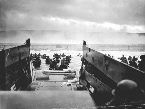 """""""אל תוך מלתעות המוות"""". חיילים אמריקאים מהנחתת סמואל צ'ייס מסתערים על חוף אומהה. מבצע אוברלורד, הפלישה לנורמנדי, 6.6.1944 (צילום: רוברט פ' סרג'נט, משמר החופים האמריקאי, נחלת הכלל)"""