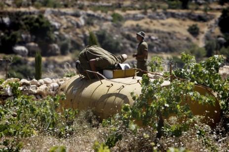 """חייל צה""""ל מתבונן בתוך מיכל מים במהלך חיפוש אחר שלושת הנערים החטופים בשדות שליד חלחול, 22.6.14 (צילום: מרים אלסטר)"""