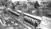 """אשה בוחנת מחירי מוצרים בסופרמרקט לאחר יישום """"עסקת חבילה א'"""", שקדמה ל""""תוכנית הייצוב"""". 6.11.1984 (צילום: חנניה הרמן, לע""""מ)"""