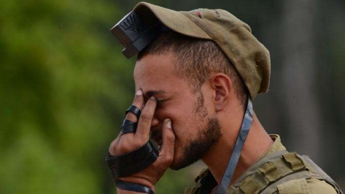 """חייל צה""""ל מניח תפילין, סמוך לגבול עם רצועת עזה, היום ה-13 למבצע צוק איתן, 20.7.14 (צילום: מנדי הכטמן)"""