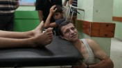 """פצוע פלסטיני מהפצצת צה""""ל בג'בליה ממתין בבית-החולים בבית-להייא, 30.7.14 (צילום: עמאד נאסר)"""
