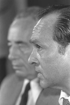 """שר האוצר יצחק מודעי, על רקע ראש הממשלה שמעון פרס, 5.11.1984 (צילום: נתי הרניק, לע""""מ)"""