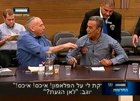 """ח""""כ יוגב מנגב את הטלפון הסלולרי שלו על חולצתו של ח""""כ זחאלקה (צילום מסך מתוך שידורי ערוץ הכנסת)"""