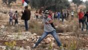 פלשתיני מיידה אבנים בהפגנה נגד גדר ההפרדה בבילעין, 1.11.2013 (צילום ארכיון: עיסאם רימאווי)