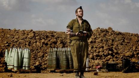 """חייל צה""""ל עטור תפילין מתפלל ליד הגבול עם רצועת עזה במהלך מבצע """"צוק איתן"""", 16.7.14 (צילום: מרים אלסטר)"""