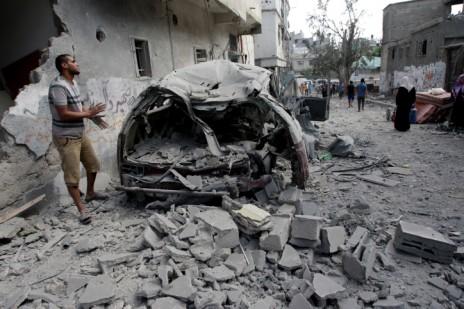 """פלסטיני בוחן את ההרס שהותירו הפגזות צה""""ל בשכונת סג'עיה שברצועת עזה במהלך מבצע """"צוק איתן"""", 26.7.14 (צילום: עבד רחים כתיב)"""