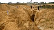 """פלשתינים בוחנים שרידי מנהרה חמאסית שנהרסה על ידי צה""""ל, רפיח, 5.8.14 (צילום: עבד רחים כתיב)"""