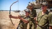 חייל ישראלי מתנסה בשימוש בקשת. פאתי עזה, 20.8.14 (צילום: אלברט סדיקוב)
