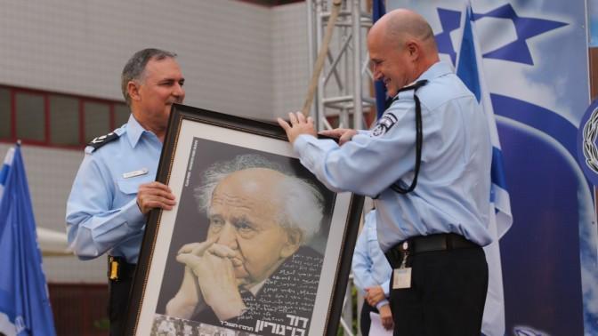 """המפכ""""ל, יוחנן דנינו, מוסר תצלום ממוסגר של ראש הממשלה הראשון של מדינת ישראל למפקד יחידת להב 433 הנכנס רוני ריטמן. 31.8.14 (צילום: פלאש 90)"""