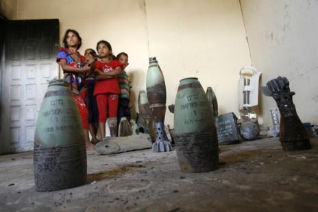 """ילדים פלסטינים מתבוננים בשרידי פצצות שאסף סולימן אבו-ג'אמה מסביב לביתו בחאן-יונס שנהרס מהפצצות צה""""ל במהלך מבצע """"צוק איתן"""", 11.9.14 (צילום: עבד רחים חטיב)"""