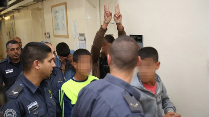 צעירים פלסטינים החשודים ביידוי אבנים, הצתת תחנת דלק ושוד חנות נוחות בשכונה יהודית במזרח ירושלים בדרכם לבית-המשפט המחוזי בעיר, 17.9.14 (צילום: נעם ריבקין-פנטון)