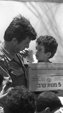 """חייל ישראלי מעניק ממתקים לילד לבנוני, צידון 1982 (צילום: יעקב סער, לע""""מ)"""