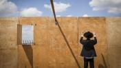 גבר חרדי מתפלל מול קיר של סוכה בבנייה. ביתר-עילית, 3.10.14 (צילום: נתי שוחט)