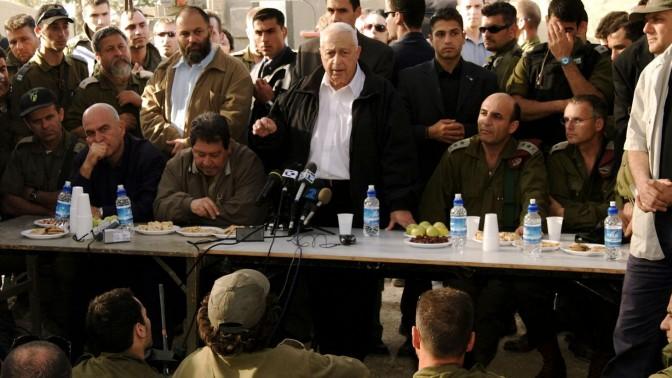"""ראש ממשלת ישראל, שר הביטחון, הרמטכ""""ל ואחרים נושאים דברים בפני חיילים ונציגי התקשורת. מבצע """"חומת מגן"""", 2002 (צילום: לע""""מ)"""