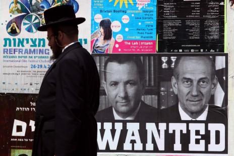 יהודי חרדי פוסע ליד מודעה שבה מופיעים אהוד אולמרט ואהוד ברק, ירושלים 2010 (צילום: אביר סולטן)