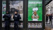 """שוטרים עומדים לצד כרזה המציגה את עמוד השער של גיליון המגזין """"שרלי הבדו"""" הראשון שיצא לאחר פיגוע הטרור במערכת העיתון, פריז, 15.1.15 (צילום: סרג' אטאל)"""