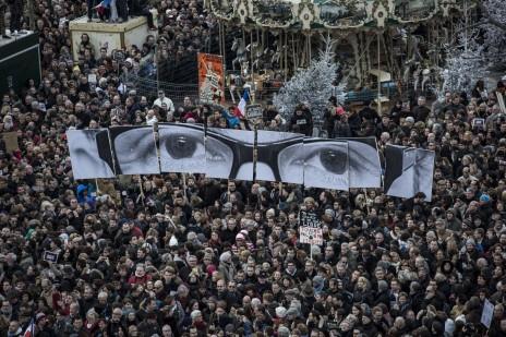"""המונים נושאים שלטים ועליהם עיניו של עורך """"שרלי הבדו"""" שנרצח, שארב. פריז, 11.1.15 (צילום: לורנס גיי)"""
