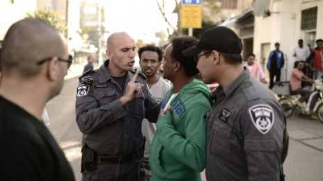 שוטרים משוחחים עם מבקש מקלט מדרום תל-אביב שעה שמועמדי מפלגת יחד מסיירים באזור, 8.3.15 (צילום: תומר נויברג)