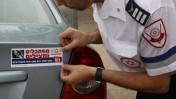 """""""מסתכלים ומצילים"""". איש מגן-דוד אדום מדביק סטיקר על מכונית, 2013 (צילום: גרשון אלינסון)"""