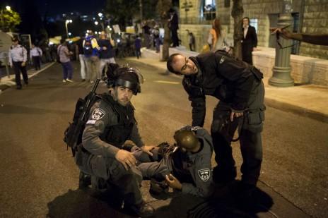 שוטרים מסייעים לעמית חבול בהפגנת בני העדה האתיופית נגד אלימות משטרתית. ירושלים, 30.4.15 (צילום: יונתן זינדל)