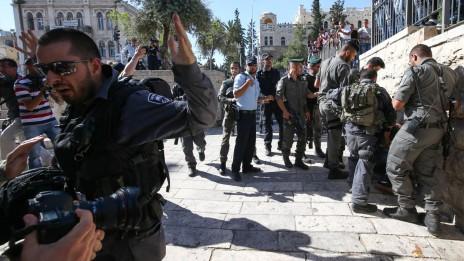 """קבוצה של שוטרים מכה פלסטיני בעת ששוטר אחר מפריע לצלמים לתעד את התקרית. שער שכם, יום ירושלים, 17.5.15 (צילום: """"העין השביעית"""")"""