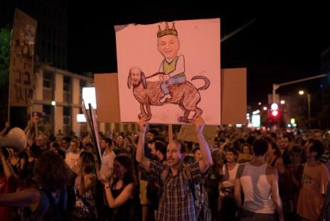 מפגין מניף קריקטורה שבה יצחק תשובה רוכב על ראש הממשלה, בנימין נתניהו, בהפגנה נגד מתווה הגז. תל-אביב, יוני 2015 (צילום: בן קלמר)