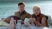 """ג'ון גודמן וריק מורניס אוכלים, מתוך הסרט """"הפלינסטונס"""" (צילום מסך)"""