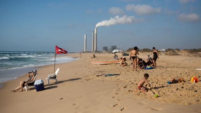ישראלים נופשים בחוף זיקים, על רקע תחנת הכוח באשקלון, 6.7.15 (צילום: מרים אלסטר)