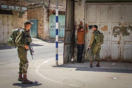 """חיילי צה""""ל מעכבים פלסטיני בעיר חברון, 10.7.15 (צילום: גארת מילס)"""