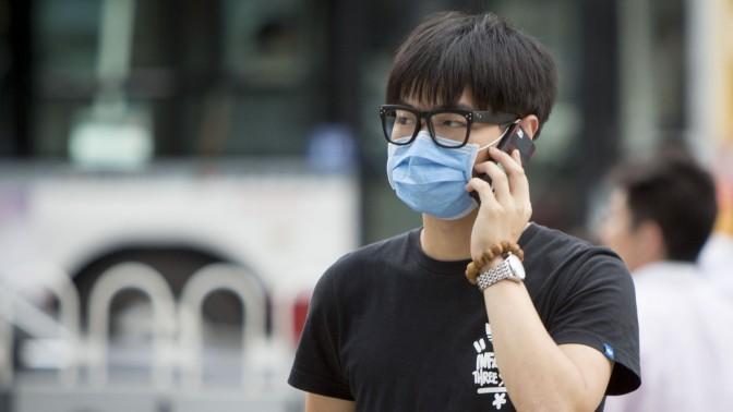צעיר סיני משוחח בטלפון בבייג'ינג, 2014 (צילום: Cylonphoto / Shutterstock)