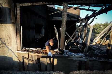 שוטר ישראלי בשרידי בית משפחת דוואבשה בכפר דומא, 31.7.15 (צילום: פלאש 90)