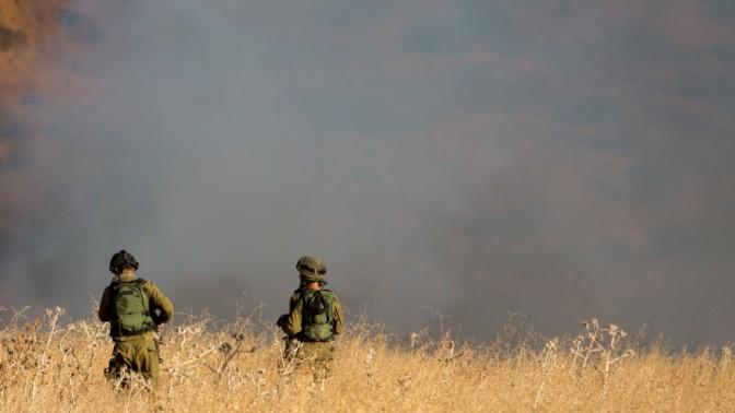 """חיילי צה""""ל מביטים בשריפה שחוללו טילים שנורו מסוריה ונחתו בגולן, 20.8.15 (צילום: באסל עווידאת)"""