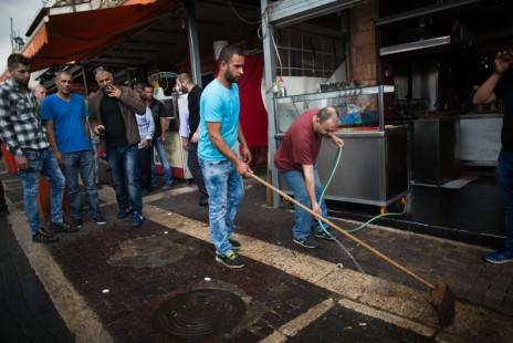 פלסטינים מנקים את הזירה ליד שער שכם שבה נורה נער פלסטיני בן 16 אחרי שדקר יהודים, 10.10.15 (צילום: יונתן זינדל)