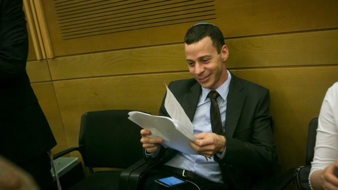 """עמית סגל מעיין בכתב התביעה שהגיש נגדו ח""""כ אורן חזן. הכנסת, 12.10.15 (צילום: מרים אלסטר)"""
