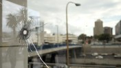 חלון מנוקב מכדור בזירת פיגוע דקירה ליד הקריה בתל-אביב, 8.10.15 (צילום: תומר נויברג)