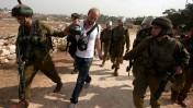 חיילים מובילים לחקירה צלם זר שנכח בהפגנה סמוך לכפר הפלסטיני נבי סלאח, 2.11.12 (צילום: עיסאם רימאווי)