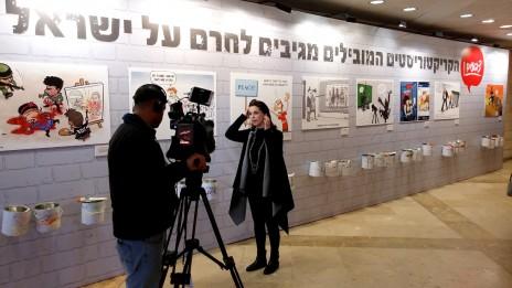 """כתבת מקליטה דיווח על רקע תערוכת הקריקטורות בכנס המאבק בחרם של קבוצת """"ידיעות אחרונות"""". בנייני-האומה, ירושלים, 28.3.16 (צילום: איתמר ב""""ז)"""