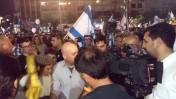 """כתב ערוץ 10 מואב ורדי מוקף מפגינים עוינים בכיכר רבין בתל-אביב, 19.4.16 (צילום: איתמר ב""""ז)"""